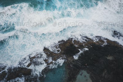 Drone view of sea waves and rocky shore