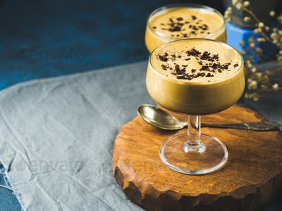 Frappe coffee in dessert glasses on brown backdrop