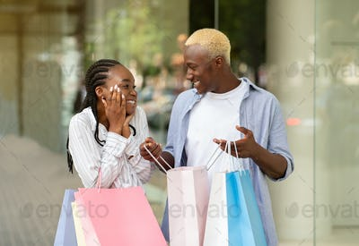 Gift for shopaholic. Cheerful african american guy shows purchases in bag, expressing happiness