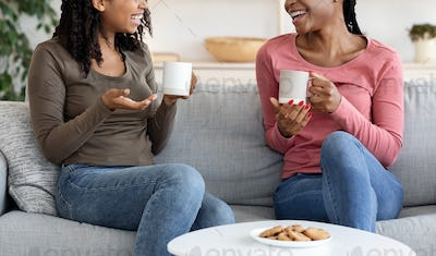 Cropped of two girls drinking coffee at home