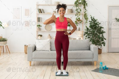 Fit African Woman Standing On Weight Scales Gesturing Thumbs-Up Indoor
