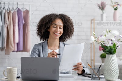 Business woman working with documents. Cheerful african american girl designer at workplace with