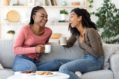Two african besties laughing while drinking tea together at home