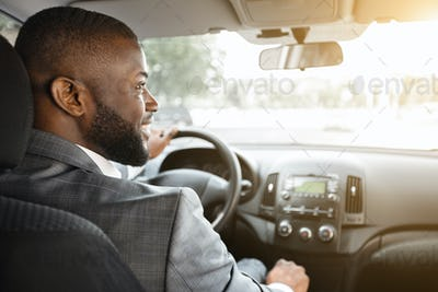 Back view of happy black businessman driving car