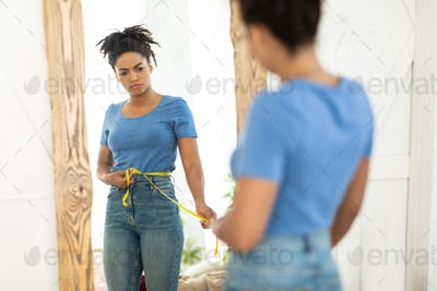 Unhappy Black Woman Measuring Waist Standing At Mirror Indoors