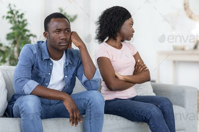 Upset black man and woman sitting on couch at home