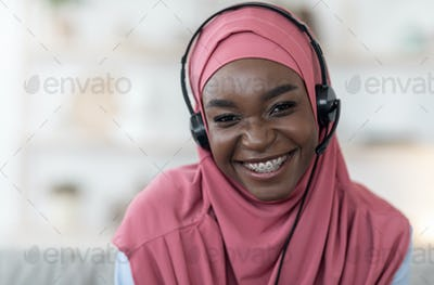 Portrait of african muslim woman in hijab and headset at home