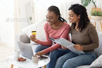 Cheerful black girls booking tickets online, using laptop