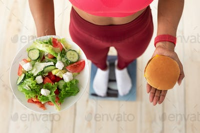 Girl Choosing Between Salad And Burger Standing On Scales Indoors