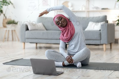 Home Training. black muslim woman in hijab practicing sports online with laptop
