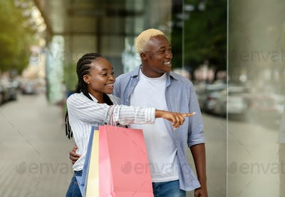 Branded product at low price. Cheerful african american couple saw discounts in shop