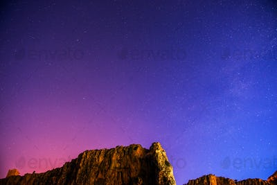 The starry sky above rocky mountains.
