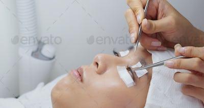 Beauty professional procedures eyelash extension on woman eyes