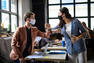 Business people with face masks greeting indoors in office, coronavirus concept