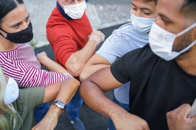 Group of people with face masks elbow bumping, coronavirus, covid-19 concept