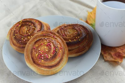 cinnamon rolls or buns with sugar sprinkle topping on white plate and cup of black tea on table