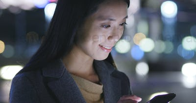 Woman look at mobile phone in city at night