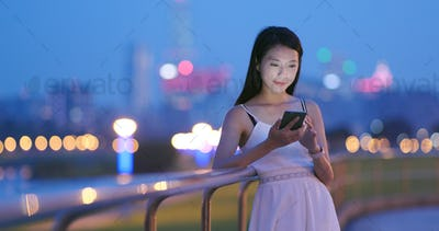 Asian woman use of mobile phone in the evening