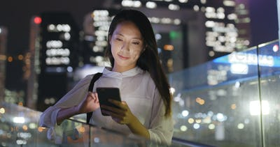 Asian Woman look at mobile phone in city at night