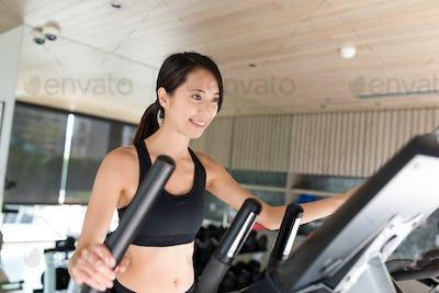 Sport Woman training on Elliptical machine in gym