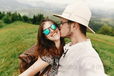 Stylish  hipster couple traveling and smiling on top of mountains in summer