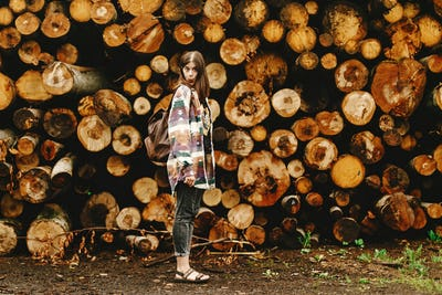 Stylish hipster woman with backpack  at pile of firewood smiling