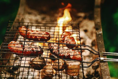 Delicious grilled sausages roasting on grates with flames and smoke