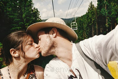 stylish hipster couple kissing on chairlift  in summer mountains