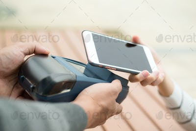 Woman pay on cellphone with NFC technology