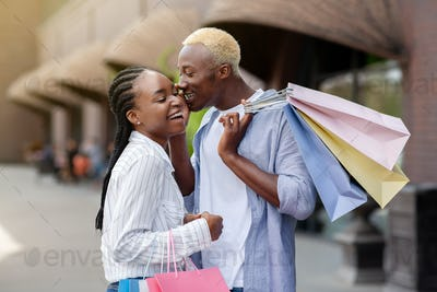 Secrets of fashion bloggers. Cheerful african american man and woman with colored packages