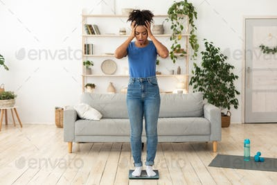 Unhappy Girl Standing On Scales Having Excess Weight Posing Indoors