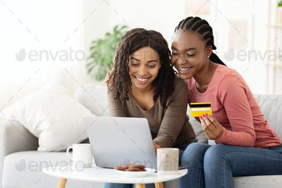 Excited black girlfriends purchasing online while drinking tea
