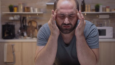 Man with headaches sitting in the kitchen