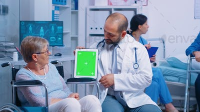 Practitioner holding mock-up tablet in recovery center for elderly disabled patients