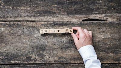 Trust us sign on wooden blocks