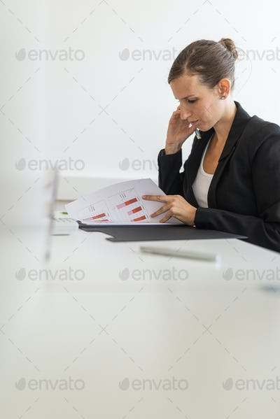 Profile view of young businesswoman sitting at her white office desk working