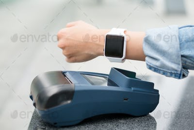 Female customer paying through smart watch by NFC