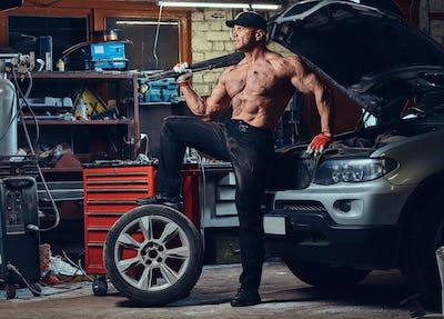 A man repairing wheel of a car.