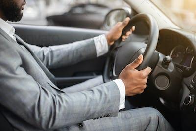 Closeup of black man in suit driving car