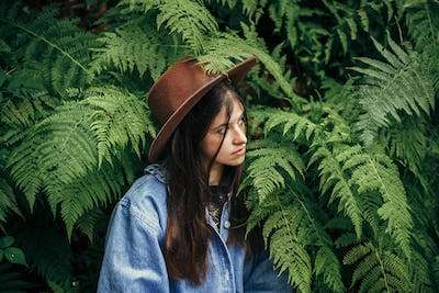 stylish hipster girl in hat sitting in fern bushes