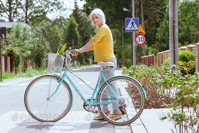Old lady in a yellow blouse crosses the street leading a blue bicycle