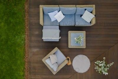 Top view of wooden terrace with comfortable wicker garden furniture