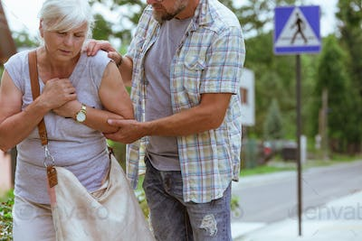 Man is supporting a senior woman feeling unwell on the street