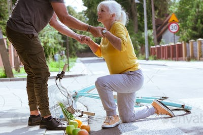 Handsome man helps an elderly woman get up after falling off a bicycle on a suburban road