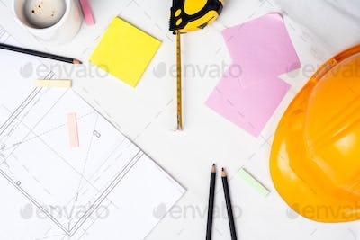Blueprints, measuring tape and helmet.