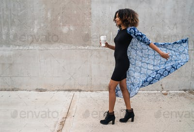 Afro-american woman walking and holding coffee.
