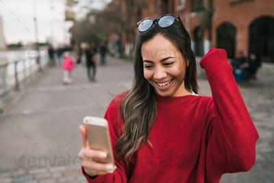 Woman holding phone with successful expression.