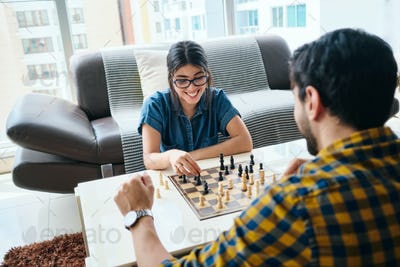 Young Couple Playing Chess Game at Home