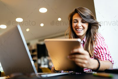 Happy young woman receiving good news on her tablet