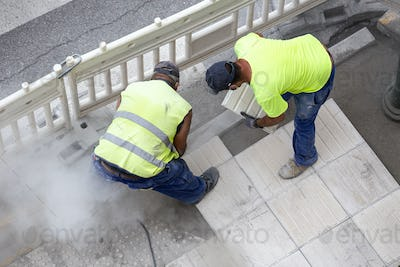 Construction workers repairing a sidewalk
